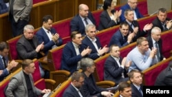 Deputies applaud after Ukraine's parliament approves a statement defining Russia as an 'aggressor state,' in Kiev, Jan. 27, 2015.