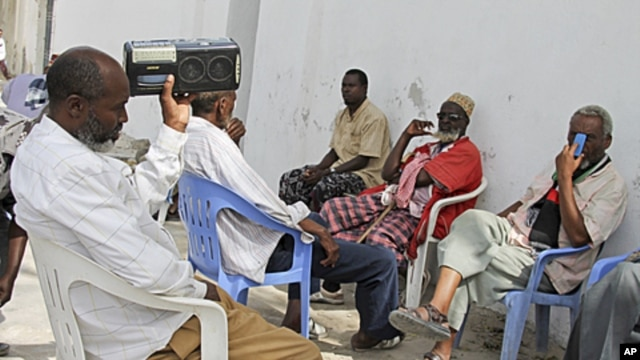 Somalis listen to news from the London conference on a radio in Mogadishu, Somalia, February 23, 2012.