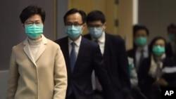 戴着口罩的香港特首林郑月娥带领港府官员步入一个新闻发布会会场。(2020年1月31日)