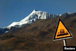 A road sign is seen in front of the Kharola glacier some 200 km (125 miles), west of Lhasa Tibet Autonomous Region, Nov. 25, 2009.