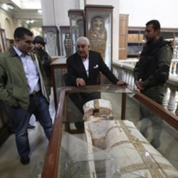 Zahi Hawass, center, standing near a damaged coffin at the Egyptian Museum in Cairo. He has announced plans to resign as head of the Ministry of State for Antiquities.