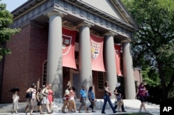 FILE - A tour group walks through the campus of Harvard University in Cambridge, Mass.