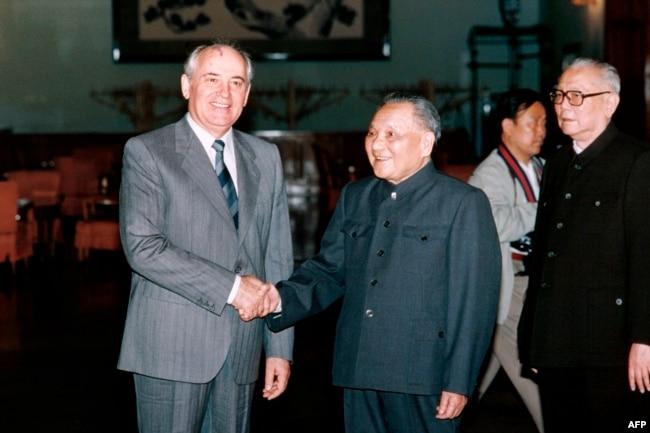 1989年5月16日中国领导人邓小平(中)与苏联共产党总书记戈尔巴乔夫(左)握手