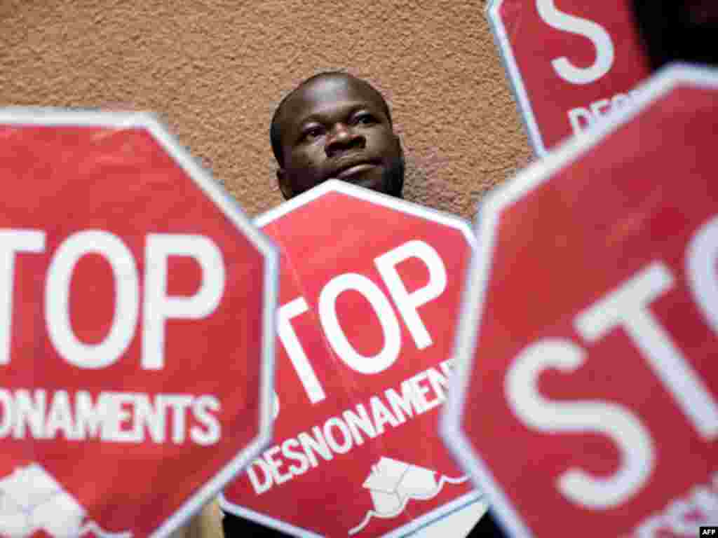 Ghanaian Wilson Yaw is seen among banners against evictions during a protest to stop the eviction of Meziane Sefioune, 34, a Moroccan citizen who is unable to pay his mortgage in Salt, Girona, Spain, Friday, Oct. 7, 2011. Dozens of evictions have been blo