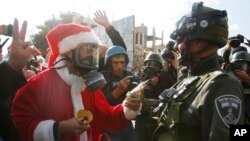 Một người biểu tình Palestine ăn mặc như ông già Noel đưa kẹo cho một cảnh sát Israel ở thành phố Bethlehem ở Bờ Tây hôm 18/12.