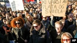 People gather to demonstrate against Iceland's prime minister, in Reykjavik on Monday April 4, 2016. Iceland's prime minister Sigmundur David Gunnlaugsson insisted Monday he would not resign after documents leaked in a media investigation allegedly link him to an offshore company. (AP Photo/Brynjar Gunnarsson)