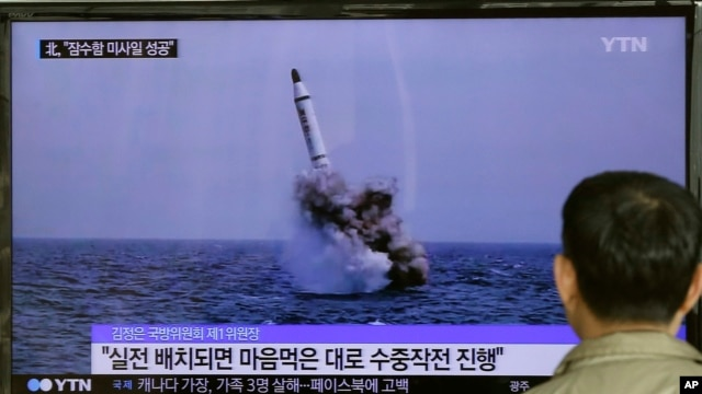 FILE - A South Korean man watches a TV news program showing an image published in North Korea's Rodong Sinmun newspaper of North Korea's ballistic missile believed to have been launched from underwater, at Seoul Railway station in Seoul, South Korea.