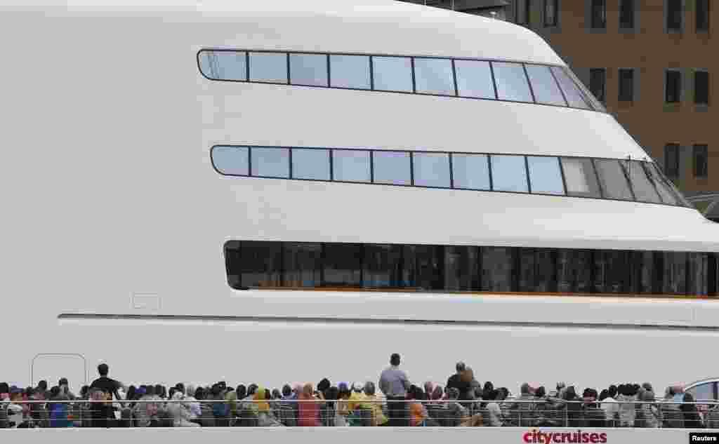 អ្នកធ្វើដំណើនៅលើកប៉ាល់ដំណើរកម្សាន្តមយយឆ្លងកាត់កប៉ាល់ដ៏ធំមួយឈ្មោះ Motor Yacht A របស់មហាសេដ្ឋីរុស្ស៊ី Andrey Melnichenko នៅក្នុងទន្លេ Thames នៅក្នុងក្រុងឡុងដ៍ ចក្រភពអង់គ្លេស កាលពីថ្ងៃទី៦ ខែកញ្ញាឆ្នាំ២០១៦។