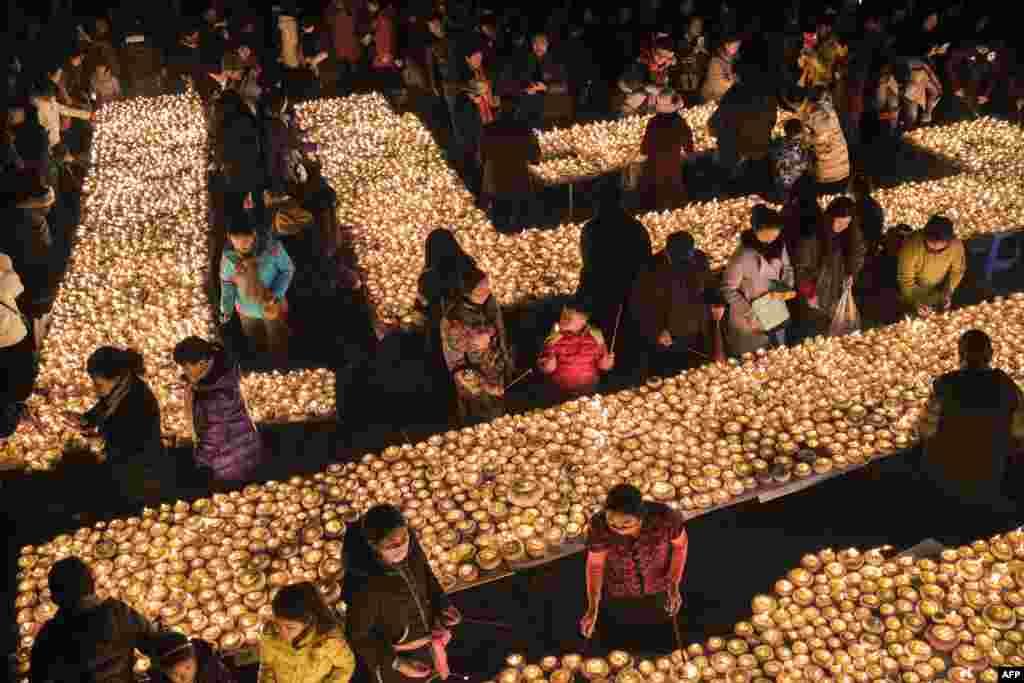 មនុស្សម្នាដុតទៀនក្នុងពិធីបុណ្យ Butter Lamp Festival ដើម្បីគោរពដល់ព្រះ Tsong Khapa ដែលជាព្រះគ្រូក្នុងសាសនាព្រះពុទ្ធនៅតំបន់ទីបេ ក្នុងតំបន់ស្វយ័តទីបេ នៅខេត្ត Sichuan ប្រទេសចិន។