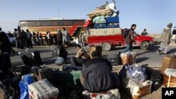Des Egyptiens de retour de Libye attendant leurs bagages à la frontière