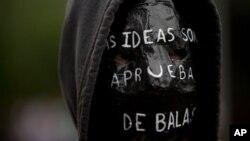 """Un manifestante exhibe durante una protesta un cartel en su mochila que dice: """"Las ideas son a prueba de bala""""."""