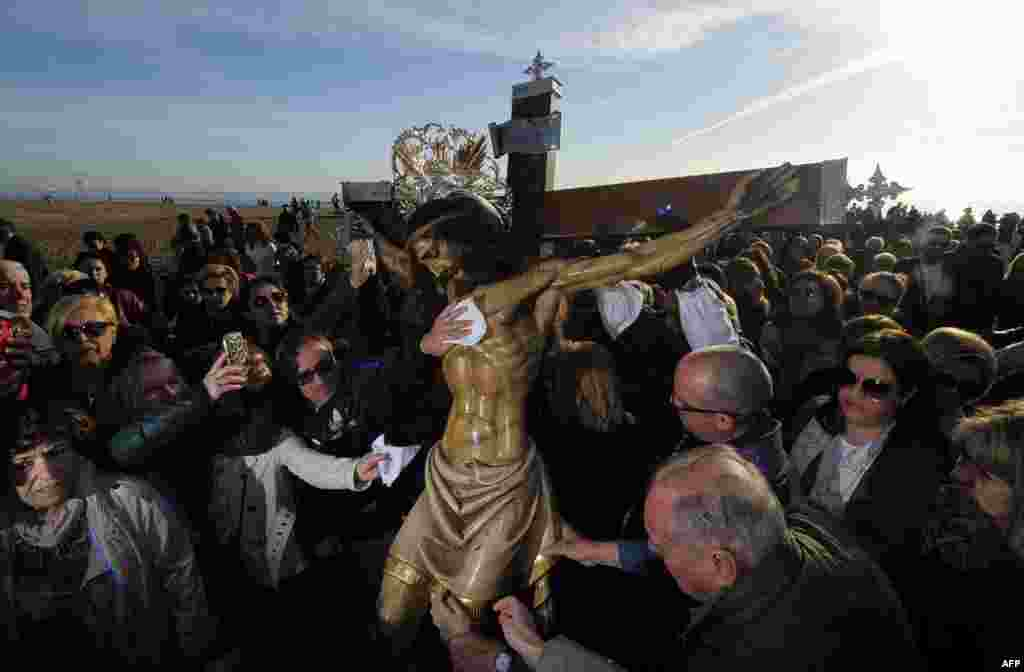 "Penitents touch the effigy of ""Cristo Salvador"" (Christ the Savior) during the Holy Week procession on the beach in Valencia, Spain, April 3, 2015."