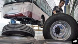 A Chinese worker moves large tires at an assembly line for buses made by Chinese auto manufacturer Foton Motor Group in Beijing (File)