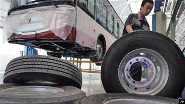 中国工人搬运汽车生产线上的轮胎(2012年)