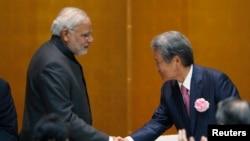 印度總理莫迪 (左) 在出席日本商業聯會午餐會並發言後與該會主席握手