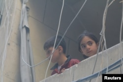 Children look out from a balcony at a site hit by airstrikes in the rebel-held area of Aleppo's Bustan al-Qasr, Syria, April 29, 2016.