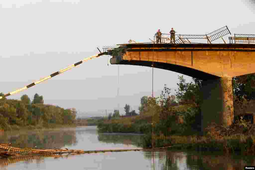 Ukrainian servicemen stand on a bridge that was ruined during battles between the Ukrainian army and pro-Russian separatists on the outskirts of Slovyansk, in the Donetsk region, Aug. 8, 2014.