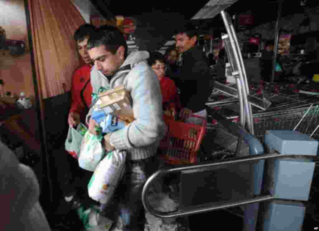 People are seen looting a supermarket in Penco, 10 kms from Concepcion, 28 Feb 2010