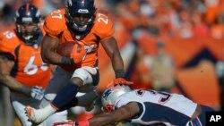Knowshon Moreno de los Broncos salta sobre Duron Harmon, de los Patriotas, en el juego que definió la Conferencia Americana.