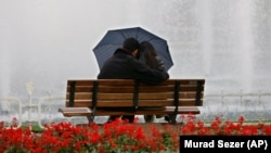 Turkish couple sit on bench under an umbrella in Turkey. (AP Photo/Murad Sezer)