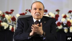 FILE - Algerian President Abdelaziz Bouteflika, sitting in a wheelchair, applauds after taking the oath as president in Algiers, April 28, 2014.