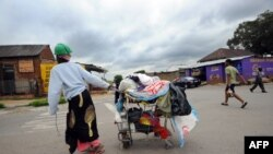 A woman collecting plastic bags carries her cart through the streets of Johannesburg's Alexandra township, December 12, 2012.