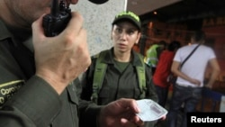 Colombian police inspect the criminal records of two men during a raid, at Comuna 20 in Cali April 12, 2013.