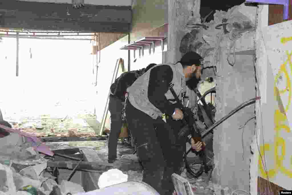 Free Syrian Army fighters inside a damaged shop in Sidi Meqdad area in the suburbs of Damascus, Syria, March 31, 2013.