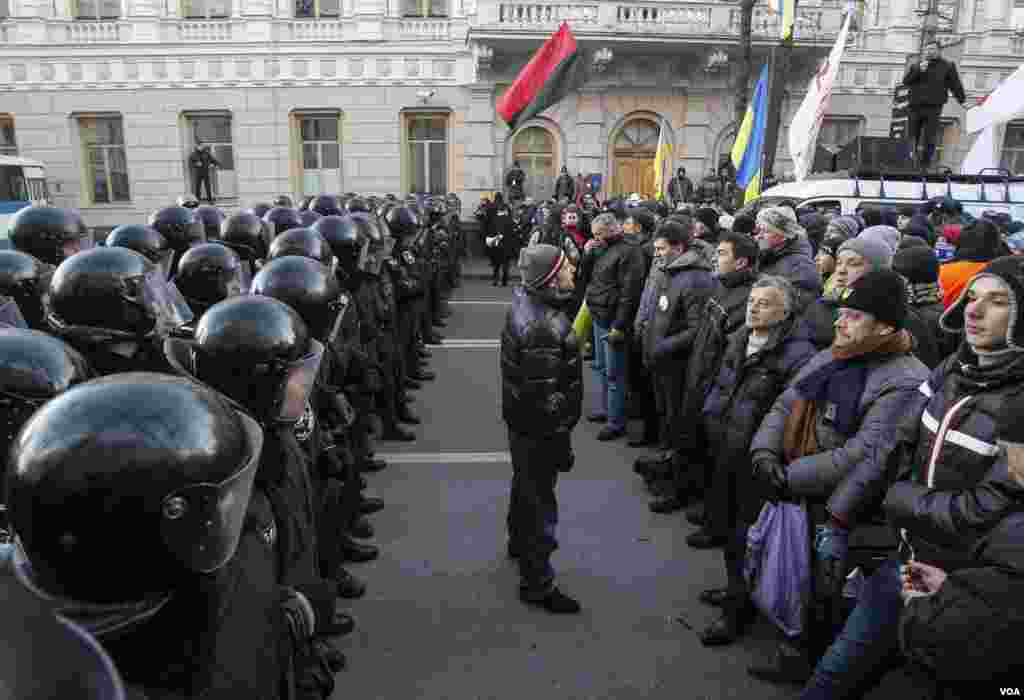 Police stand guard in front of protesters during a demonstration in support of EU integration in front of parliament in Kyiv, Dec. 3, 2013.