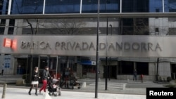 FILE - A couple walk past a Banca Privada d'Andorra (BPA) office in Andorra la Vella, March 29, 2015.