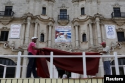 Workers make final touches to one of the podiums near Havana's cathedral, that will be used during the visit of Pope Francis to Cuba, Sept. 17, 2015.