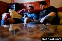 Mino Zuniga Gonzales, 19, left, and his brother Erick Zuniga Gonzales, 17, look at a smart phone in the Kensington section of Philadelphia, Sunday, May 16, 2021.