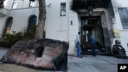 FILE - Two men look at the damage to the entrance of the Chinese Consulate in San Francisco on Thursday, Jan. 2, 2014.