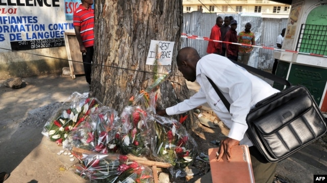 A man lays flowers at a tree on the street of Abidjan where at least 60 persons died in a stampede among crowds gathered for celebratory New Year's Eve fireworks, January 2, 2013.