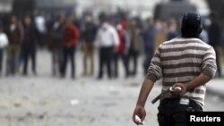 Một người biểu tình cầm một khẩu súng tự chế trong cuộc đụng độ với cảnh sát chống bạo động trên cầu Qasr Al Nil dẫn đến Quảng trường Tahrir ở Cairo ngày 27/1/2013.