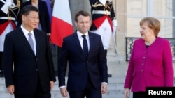 French President Emmanuel Macron, German Chancellor Angela Merkel and Chinese President Xi Jinping leave following a meeting at the Elysee Palace in Paris, France, March 26, 2019.