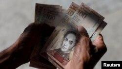 A man counts Venezuelan bolivar notes in downtown Caracas, Venezuela, Jan. 9, 2018.