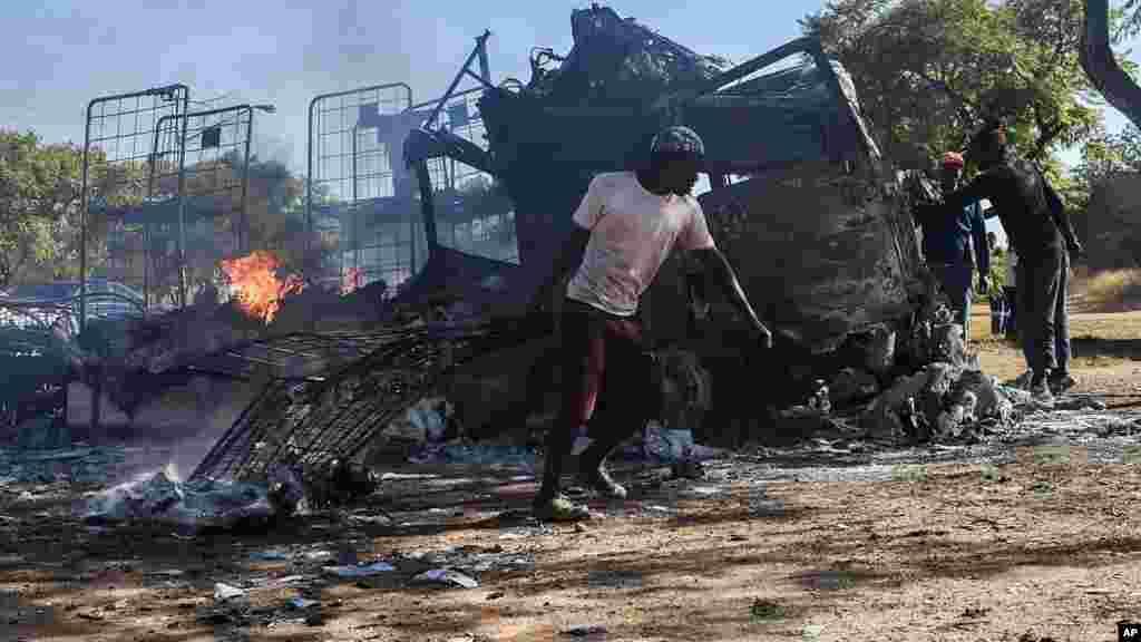 Un habitant passe devant un camion incendié près de la route où les manifestants sont passés à Atteridgeville, à l'ouest de Pretoria, Afrique du Sud, le 21 juin 2016.