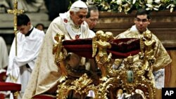 Pope Benedict XVI kneels in prayer as he celebrates Christmas Mass in St. Peter's Basilica at the Vatican, 24 Dec 2010