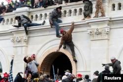 مظاہرین پولیس کی رکاوٹیں پھلانگ کر عمارت پر چڑھ گئے۔ 6 جنوری 2021