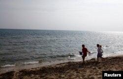 FILE - Children play at a beach in Hammamet, Tunisia, Feb. 19, 2013.