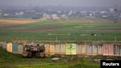 An Israeli tank is positioned outside the northern Gaza Strip, March 13, 2014.