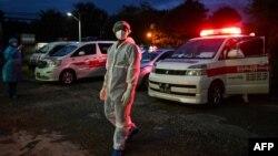 ရန္ကုန္ၿမိဳ႕ရွိ လမ္းတခုတြင္ ကိုဗစ္သံသယရွိလူနာမ်ားကို Quarantine စင္တာဆီ ေခၚေဆာင္ဖို႔ ေစာင့္ေနသည့္ PPE ဝတ္စံုဝတ္ ပရဟိတလုပ္သားတစ္ဦး။ (ေအာက္တုိဘာ ၁၊ ၂၀၂၀)