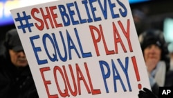 FILE - A girl holds up a sign for equal pay for the U.S. women soccer players, April 4, 2017, during a soccer match between the United States and Colombia, in East Hartford, Conn. A new study finds women are just as ambitious as men, but fall behind if their employer isn't encouraging. That gap often leads to a pay gap.