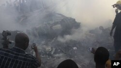People use mobile phones to photograph wreckage of Dana Air flight 9J-922, Lagos, Nigeria, June 3, 2012.