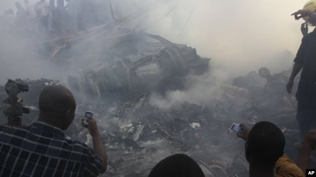 People use mobile phones to photograph wreckage of Dana Air flight 9J-922, Lagos, Nigeria, June 3, 2012.