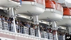 People aboard the disabled Carnival Splendor cruise ship watch as they approach a dock in San Diego on 11 Nov 2010
