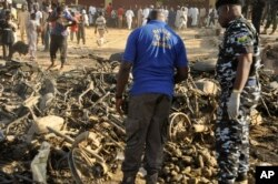 Nigerian police inspect the site of an explosion in Kano, Nigeria, Nov. 28, 2014.