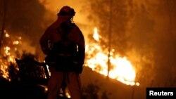 ایک فائر فائٹر آگ کے شعلوں کو دیکھ رہا ہے ۔ جنگل میں بھڑکنے والی یہ آگ کیلی فورنیا کے شہر ریڈنگ کی جانب بڑھ رہی ہے۔ 27 جولائی 2018