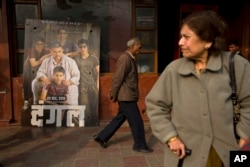 An elderly man walks past a poster of Bollywood movie Dangal, a 2016 Bollywood biopic on an Indian wrestling coach and his two professional wrestler daughters, outside a theater in New Delhi, India.
